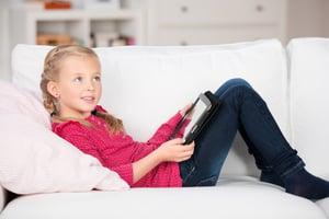 modern kid with digital pad lying on sofa